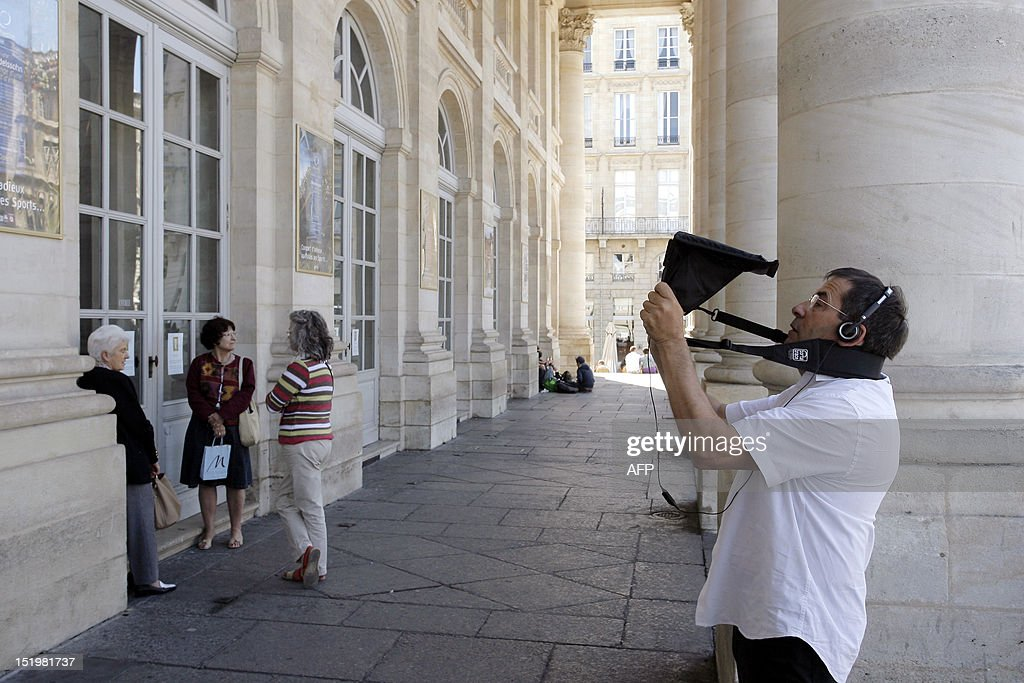 A tourist watches the screen of a tablet as he visits the French southwestern city of Bordeaux on September 14, 2012. The tablet, which uses augmented reality technology, displays images of monuments and historical characters of the 18th century while the visitor walks in the city streets.