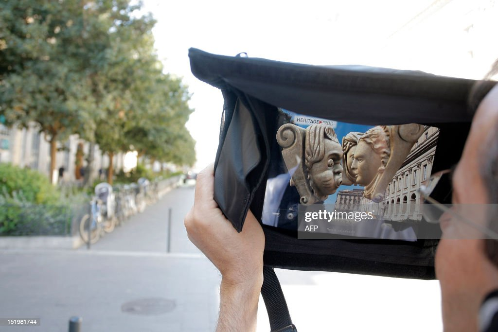 A tourist watches the screen of a tablet as he visits the French southwestern city of Bordeaux on September 14, 2012. The tablet, which uses augmented reality technology, displays images of monuments and historical characters of the 18th century while the visitor walks in the city streets. AFP PHOTO / NICOLAS TUCAT