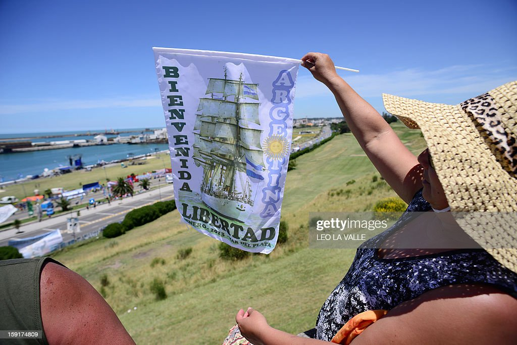 A tourist waves a flag before the arrival of the frigate Libertad at the Argentinean Navy base of Mar del Plata, 410 Km southwest of Buenos Aires on January 9, 2013. The Libertad was detained for two months in Ghana due to a debt the Argentine government has held with a financial fund since they defaulted during an economic crisis in 2001. The ship is set to arrive in Mar del Plata, Argentina on January 9. AFP PHOTO/Leo La Valle