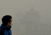 A tourist wearing a face mask climbs Jingshan Hill beside the Forbidden City as heavy air pollution continues to shroud Beijing on February 26 2014...