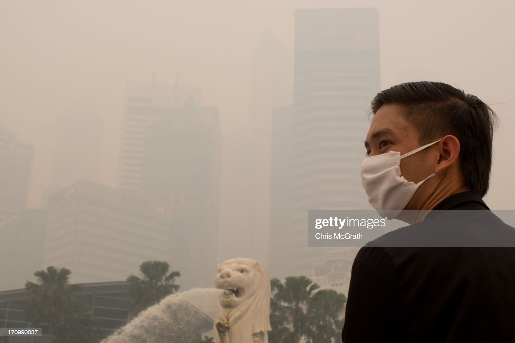A tourist wearing a mask looks out over the Singapore skyline which is barely visible due to being shrouded in thick smoke haze on June 21, 2013 in Singapore. The Pollutant Standards Index (PSI) rose to the highest level on record reaching 400 at 11am. The haze is created by deliberate slash-and-burn forest fires started by companies in neighbouring Sumatra.