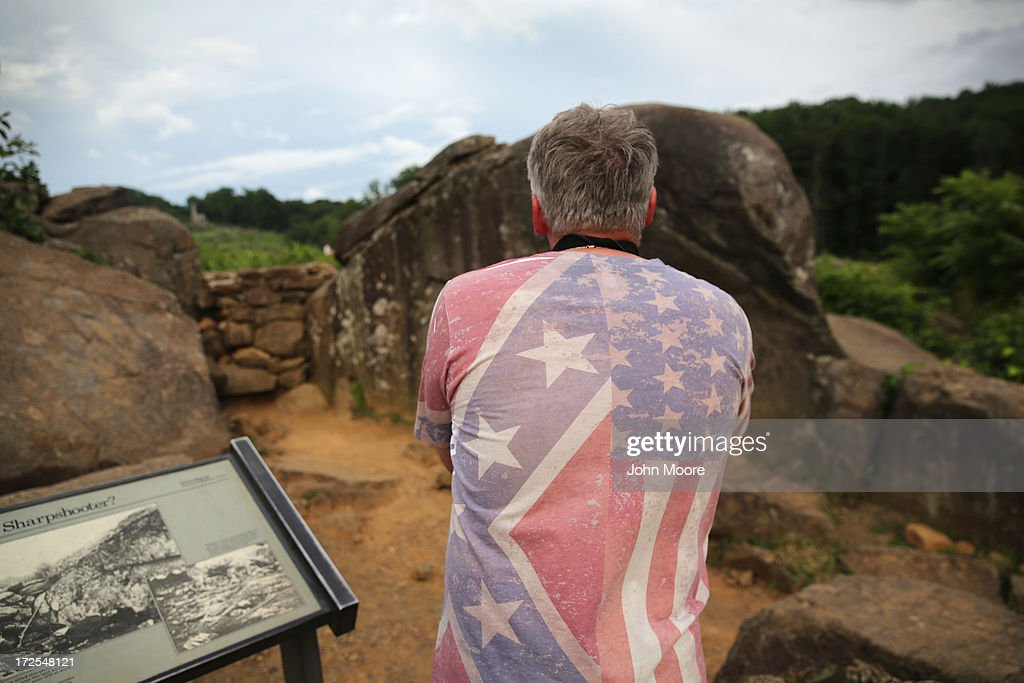 A tourist wearing a shirt featuring the Confederate and American flags photographs at Devil's Den on July 2, 2013 in Gettysburg, Pennsylvania, the 150th anniversary of the Battle of Gettysburg. Many tourists visiting the site pose for photos there as part of their battlefield experience. An historic photo entitled 'The Home of a Rebel Sharpshooter' was taken there by Alexander Gardner on July 5, 1863 and featured a dead Confederate soldier with a rifle proped next to him. The photograph was later discovered to be staged, the dead body of the 'sharpshooter' having been brought from another place on the battlefield for the photograph and the gun not a sharps rifle.