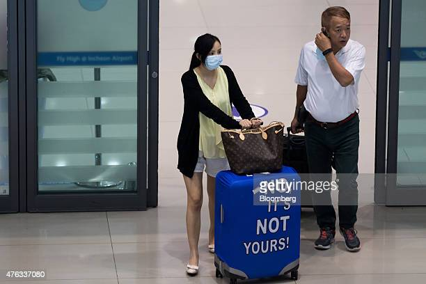 A tourist wearing face masks exits a gate at Incheon International Airport in Incheon South Korea on Monday June 8 2015 South Korea reported its...
