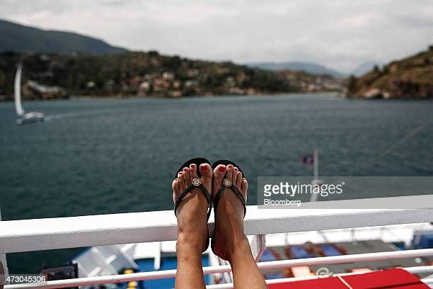 A tourist wearing sandals relaxes as she sails aboard a cruise ship in the Saronic gulf west of Athens Greece on Monday May 11 2015 Less than three...