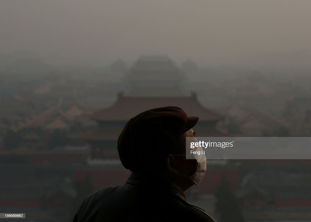A tourist wearing the mask looks at the Forbidden City as pollution covers the city on January 16, 2013 in Beijing, China. Heavy smog shrouded Beijing with pollution at hazardous levels from January 12.