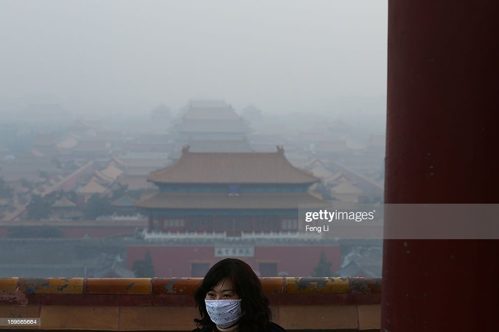 A tourist wearing the mask looks on as pollution covers the Forbidden City on January 16, 2013 in Beijing, China. Heavy smog shrouded Beijing with pollution at hazardous levels from January 12.