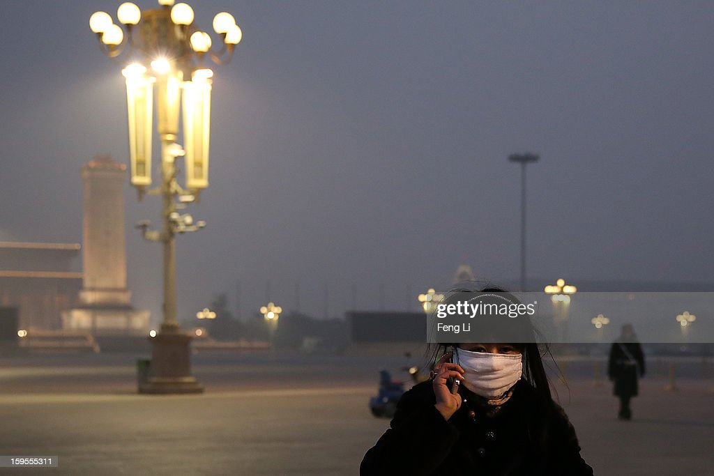 A tourist wearing the mask phones at the Tiananmen Square during severe pollution on January 13, 2013 in Beijing, China. Heavy smog shrouded Beijing with pollution at hazardous levels from January 12.