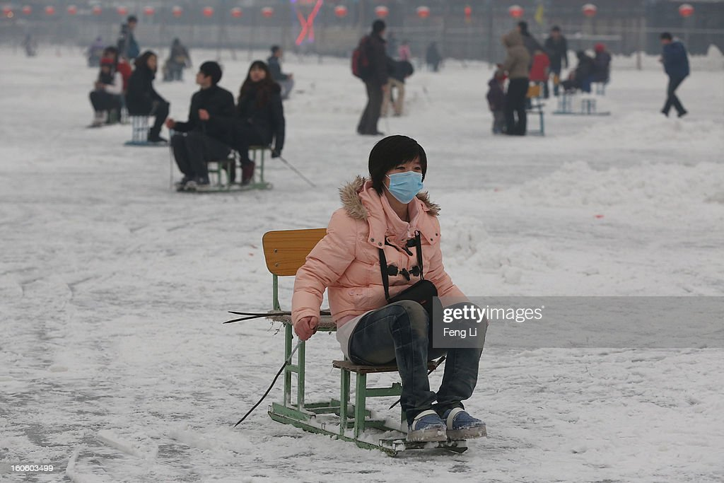 A Tourist wearing the mask rides on specially constructed 'ice-chairs' on the frozen Houhai Lake during severe pollution on February 3, 2013 in Beijing, China. Houhai Lake is a popular place for winter sport and entertainment in Beijing.