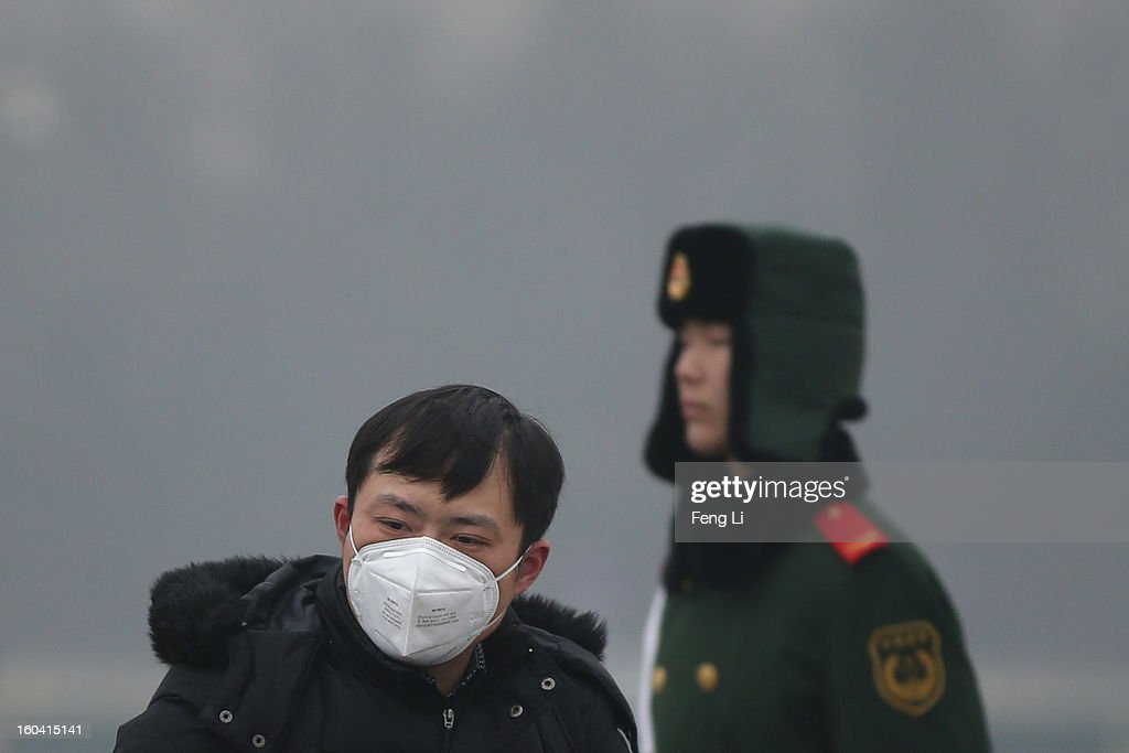 A tourist wearing the mask visits the Tiananmen Square as a policeman guarding during severe pollution on January 31, 2013 in Beijing, China. Heavy smog that has choked Beijing for the last five days weakened slightly on Thursday due to a light rainfall, although the capital's air remains heavily polluted. The haze choking many Chinese cities covers a total area of 1.43 million square kilometers, the China's Ministry of Environmental Protection said Wednesday.