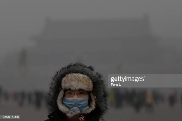 A tourist wearing the mask visits the Tiananmen Square at dangerous levels of air pollution on January 23 2013 in Beijing China The air quality in...