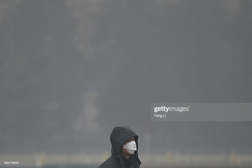 A tourist wearing the masks walks on the Tiananmen Square during severe pollution on January 31, 2013 in Beijing, China. Heavy smog that has choked Beijing for the last five days weakened slightly on Thursday due to a light rainfall, although the capital's air remains heavily polluted. The haze choking many Chinese cities covers a total area of 1.43 million square kilometers, the China's Ministry of Environmental Protection said Wednesday.
