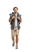 Full length portrait of a tourist with a backpack walking towards the camera isolated on white background