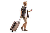 Full length profile shot of a tourist with a passport and a suitcase walking isolated on white background