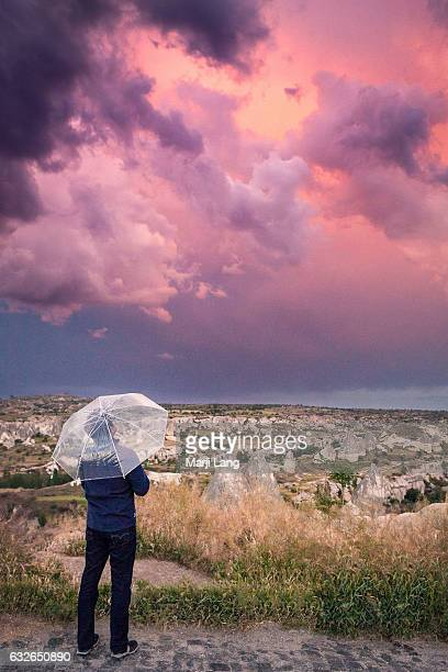 Tourist with an umbrella watching the cloudy sky and rocky landscape of Cappadocia Turkey