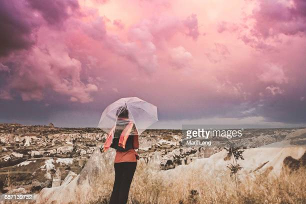 Tourist with an umbrella watching the stormy sky and rocky landscape of Cappadocia Turkey