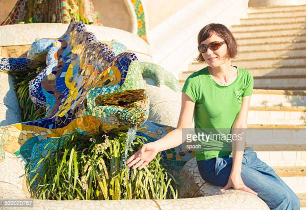 Tourist with Gaudi's lizard in Parc Guelle in Barcelona