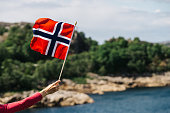 Tourist hand holding norwegian flag on rocky stone sea coast background.