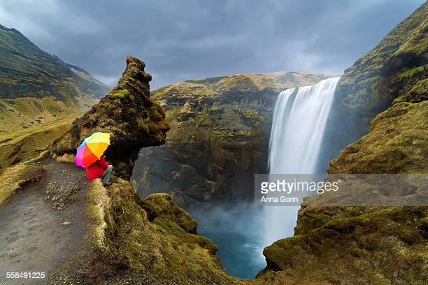 Tourist with rainbow umbrella sits by Skogafoss