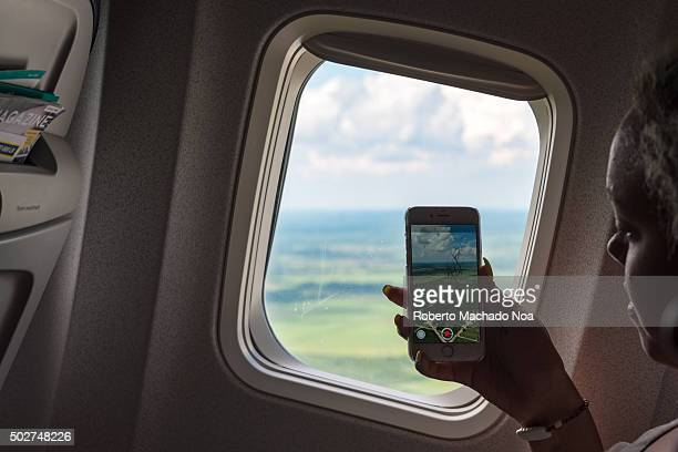 Tourist woman taking picture with cell from an airplane taking off in Cuba