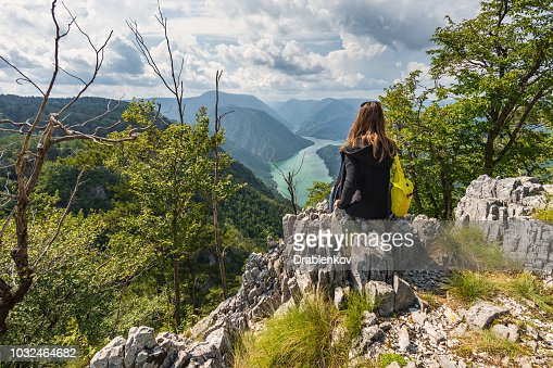 A tourist woman with a backpack sits on top of the mountain on Banjska Stena viewpoint : Stock Photo