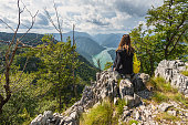 A tourist woman with a backpack sits on top of the mountain on Banjska Stena viewpoint and looks ahead at the beautiful view in the distance, the mountains and the Drina River