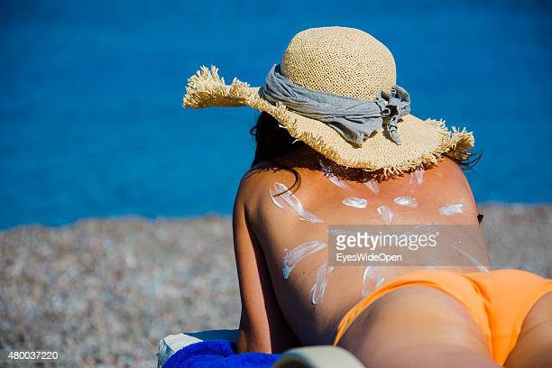 Tourist woman with a sun painted with sun creme on her back a sunhat on a sunbed at the beach on June 28 2015 in Lahaina Rhodes Dodecanes Greece