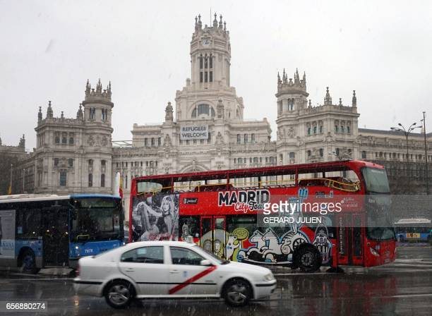 A touristic bus a regular cityline bus and a taxi pass under the snow with the Palacio de Cibeles City Hall of Madrid in background on March 23 2017...