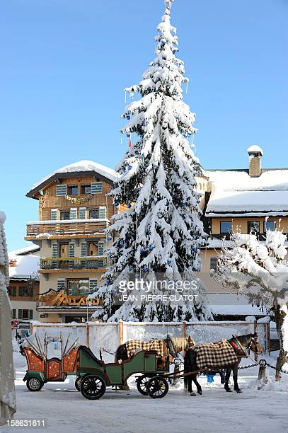 EMONET Touristic horsedrawn carriages wait for clients on December 19 2012 in the French luxury ski ressort of Megeve French Alps AFP PHOTO /...