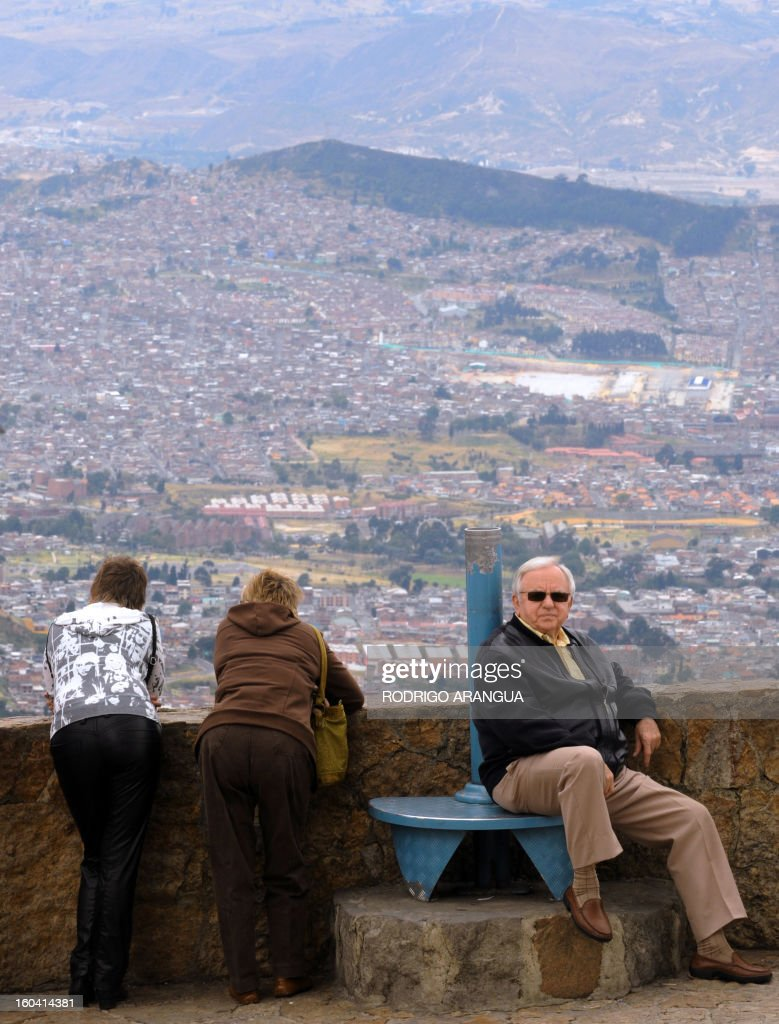 Tourists admire a view of Bogota from the Monserrat Hill in Bogota on February 9, 2010. AFP PHOTO/Rodrigo ARANGUA /