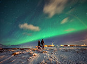 Tourists stand in awe under the beautiful northern lights (aurora borealis) under the jagged mountains of the Lofoten Islands.  Reine, Norway