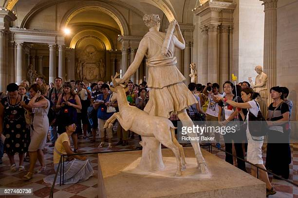 Tourists admire the statue of Diana of Versailles a slightly over lifesize marble statue of the Greek goddess Artemis with a deer located in the...