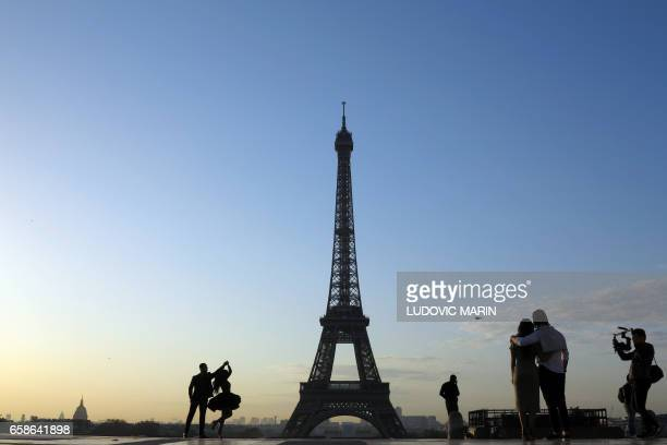 Tourists and a young married couple are pictured at sunrise on the Esplanade du Trocadero near the Eiffel tower on March 28 2017 in Paris / AFP PHOTO...