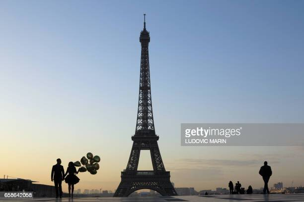 Tourists and a young married couple is pictured at sunrise on the Esplanade du Trocadero near the Eiffel tower on March 28 2017 in Paris / AFP PHOTO...
