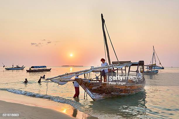 Tourists and Dhow boat at sunset on beach