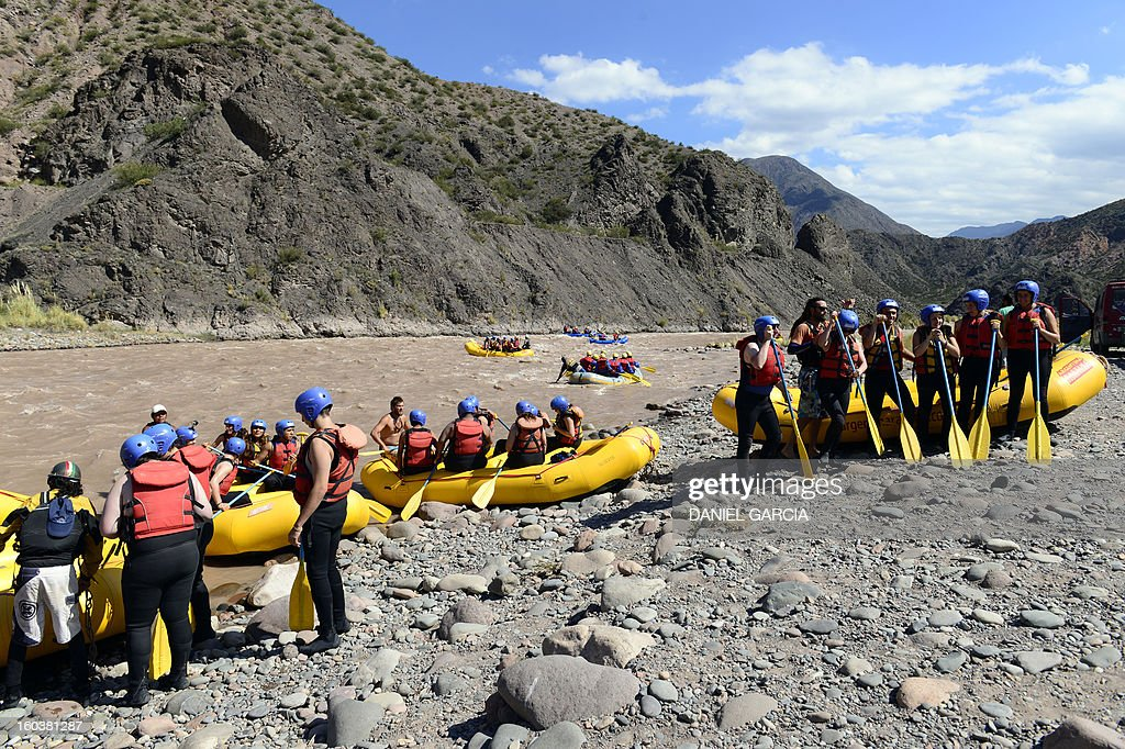 Tourists and guides embark on the rafts to go rafting through the rapids in the muddy waters of the Mendoza river near Potrerillos, Argentina on January 29, 2013.
