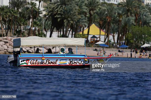 Tourists and Jordanians sit in a glass bottomed boat as they enjoy the sun and sea during the weekend on April 4 2015 in the southern city of Aqaba...
