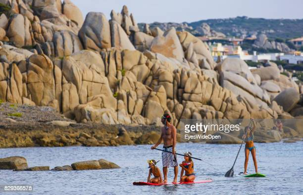 Tourists and local people enjoy standup paddling in the sun at Capo Testa beach on September 9 2014 in Cagliari Sardinia Italy