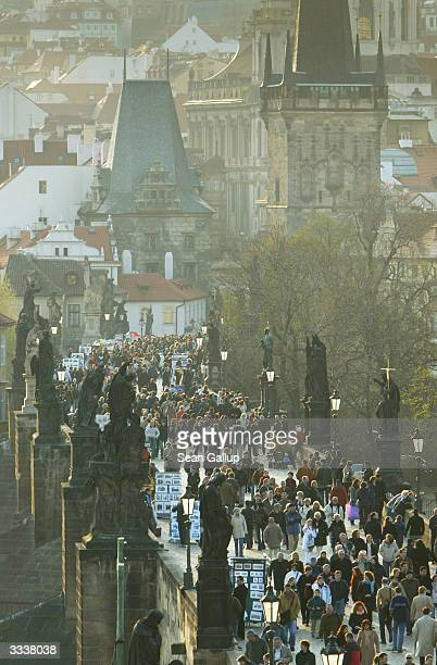 Tourists and locals crowd the historic Charles Bridge on April 10 2004 in Prague Czech Republic Prague remains one of the most popular tourist...