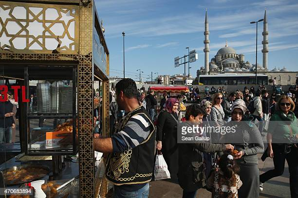 Tourists and locals pass by food stands near Galata Bridge as the New Mosque stands behind on April 1 2015 in Istanbul Turkey Istanbul is a popular...