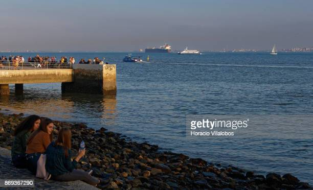 Tourists and locals relax by the river in Cais do Sodre on October 31 2017 in Lisbon Portugal Although active all year round Portuguese tourist...