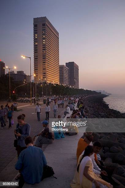 Tourists and locals relax on the Marine Drive promenade in front of the Trident Hotel one of the sites of the 2008 terrorist attacks in Mumbai India...