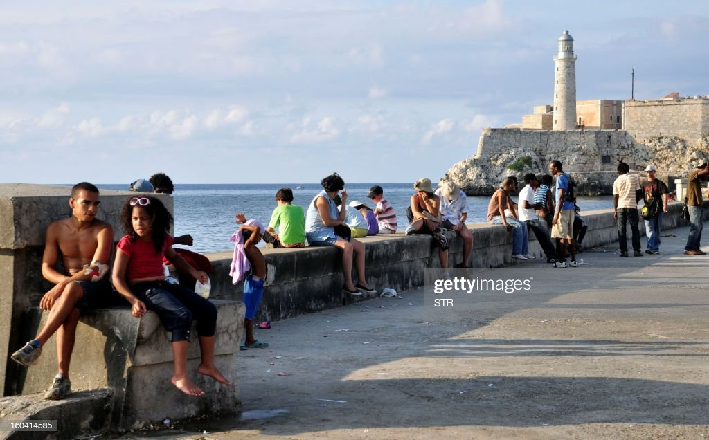 Tourists and locals sit on the wall of the waterfront near the Morro lighthouse in Old Havana, Cuba, on August 25, 2010.