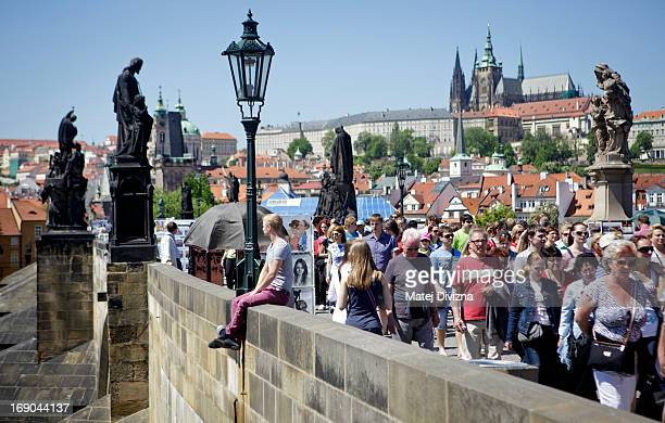 Tourists and locals walk across the medieval Charles Bridge on May 15 2013 in Prague Czech Republic The Prague Castle is in the background Prague is...