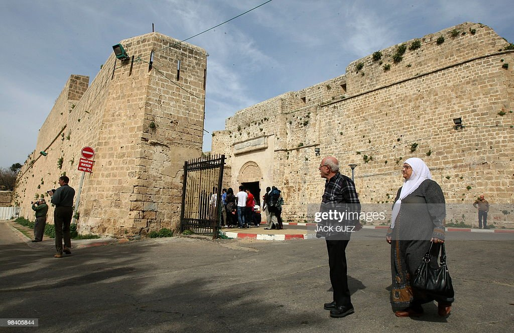 Tourists and locals walk near Akko's Old City walls in the ancient Mediterranean town of Akko north of Haifa Israel on February 17 2010 The first...
