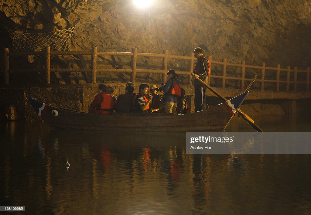 Tourists and members of the press ride in small rowing boats inside the Beihai Tunnel on May 8, 2013 in Nangan, Matsu Islands, Taiwan. The tunnel was once part of a military base but now is a popluar tourist spot on Matsu Island. The military held a routine drill today on an unnamed base on the island which was opened up to the press by the Ministry of National Defence.