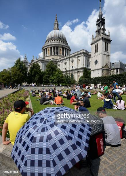 Tourists and office workers in Festival Gardens enjoy the warm weather as they eat their lunch in the shadow of St Paul's Cathedral London