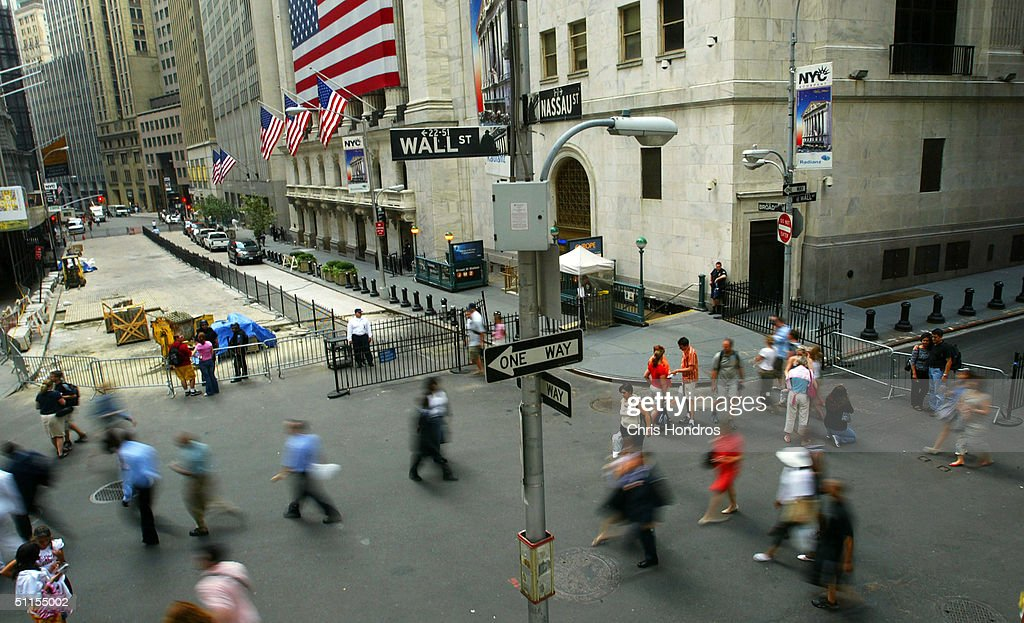 Tourists and office workers tool around at the corner of Wall and Broad Streets in front of the New York Stock Exchange August 9, 2004 in New York City. Government officials have warned that intelligence points toward terrorists considering using tourist helicopters and Manhattan's ubiquitous limousine cars as possible attack vehicles on the city.
