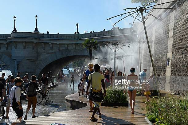 Tourists and Parisians cool down under jets of water at Paris Plage on the right banks of the Seine River on August 1 2013 in Paris France