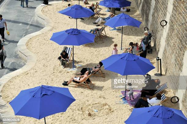 Tourists and Parisians take advantage of 'Paris Plage' an artificial beach set up on the right bank of the River Seine on August 14 2014 in Paris...