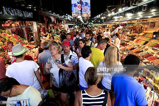 Tourists and pedestrians fill an aisle between food stalls inside Boqueria market in Barcelona Spain on Thursday Aug 25 2016 'Consumption has been...